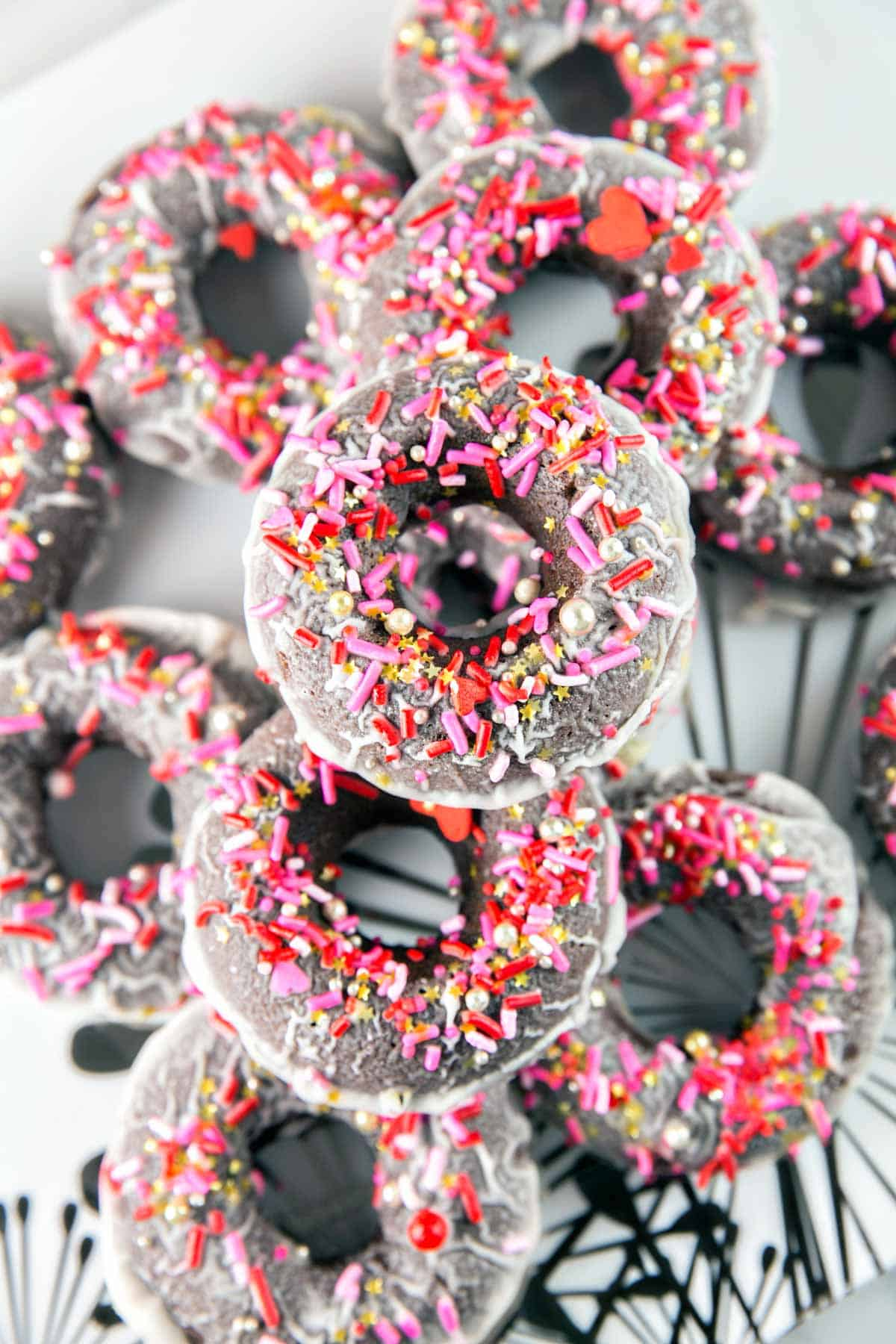 a stack of baked peppermint mocha donuts covered in sprinkles on a serving plate