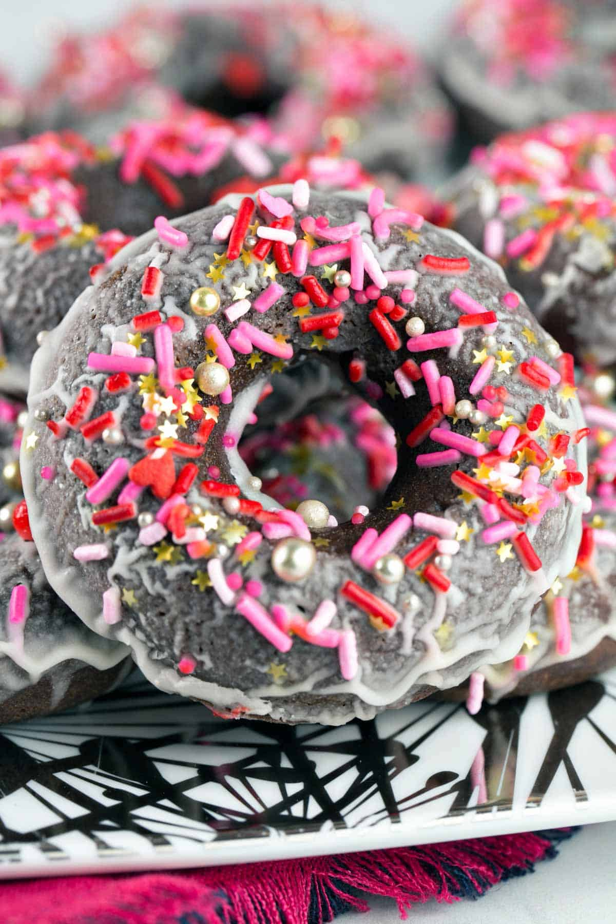 close up photo of a baked peppermint mocha donut covered in pink white and gold sprinkles