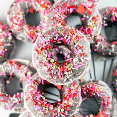 Baked Peppermint Mocha Donuts: chocolatey, cake, baked peppermint mocha donuts, dunked in a peppermint mocha glaze and covered with festive sprinkles. Perfect for holiday entertaining, any time of day! #bunsenburnerbakery #donuts #cakedonuts #peppermintmocha #christmas