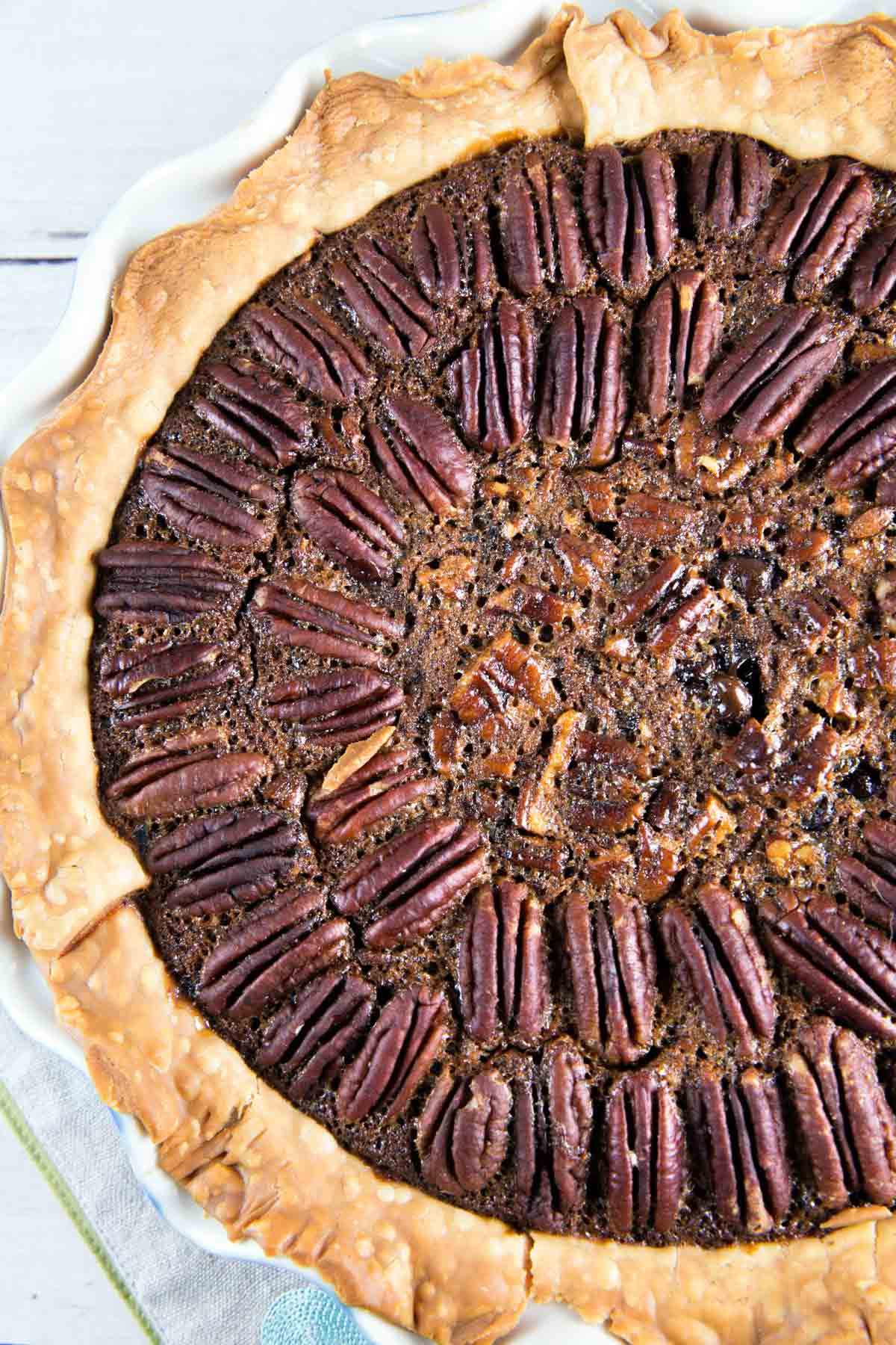 overhead closeup of a chocolate bourbon pecan pie with pecans arranged in concentric circles