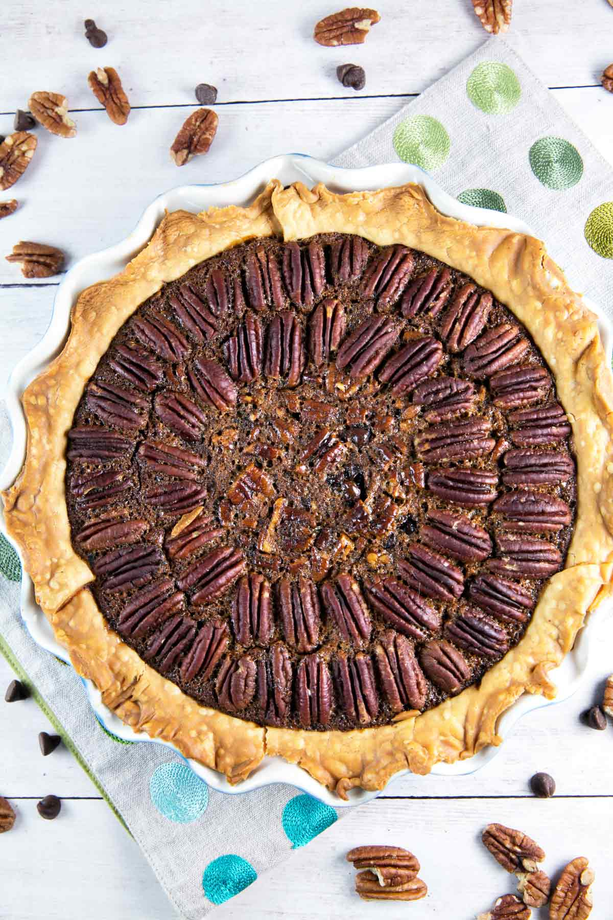 overhead view of a whole chocolate bourbon pecan pie with pecans arranged decoratively on the surface