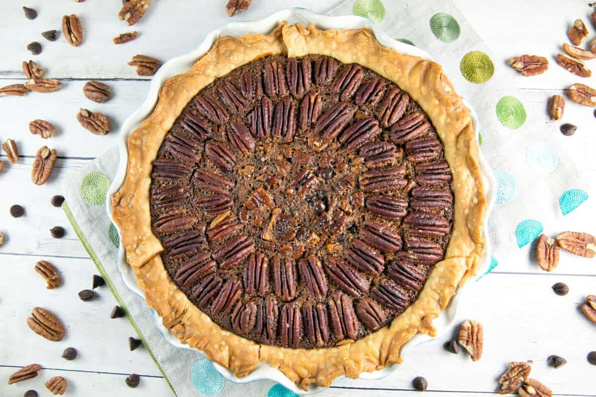 overhead view of a baked chocolate bourbon pecan pie with pecans scattered in the background