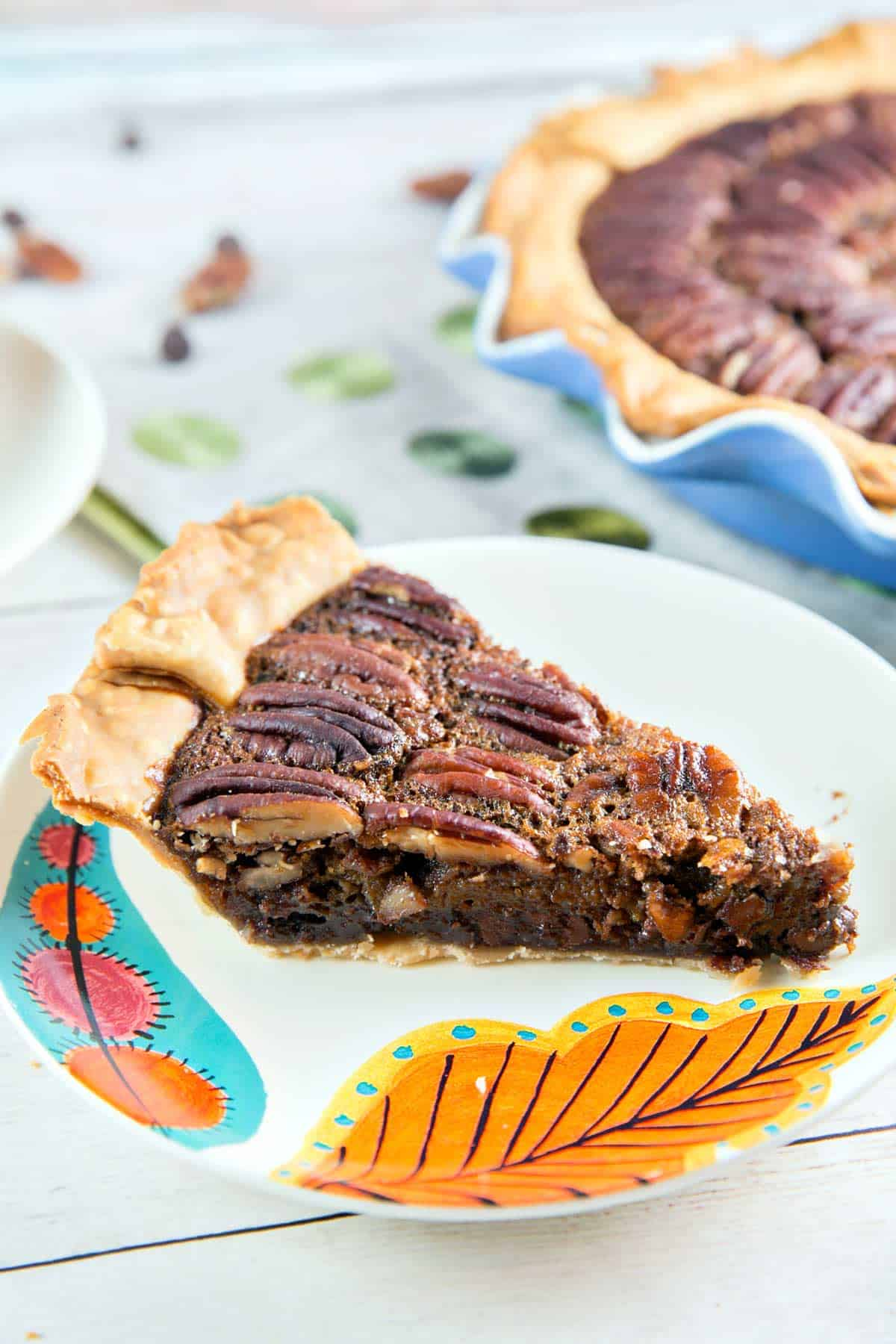 side view of a slice of chocolate bourbon pecan pie on an orange leaf plate