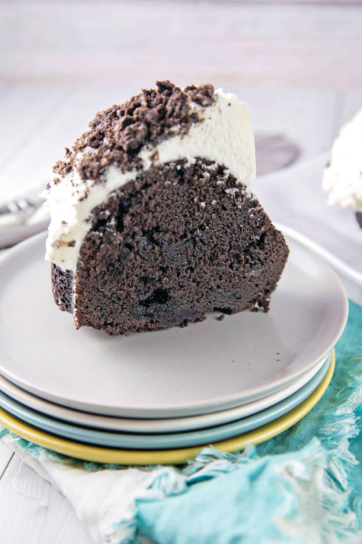 single slice of a dark black chocolate oreo bundt cake with white frosting