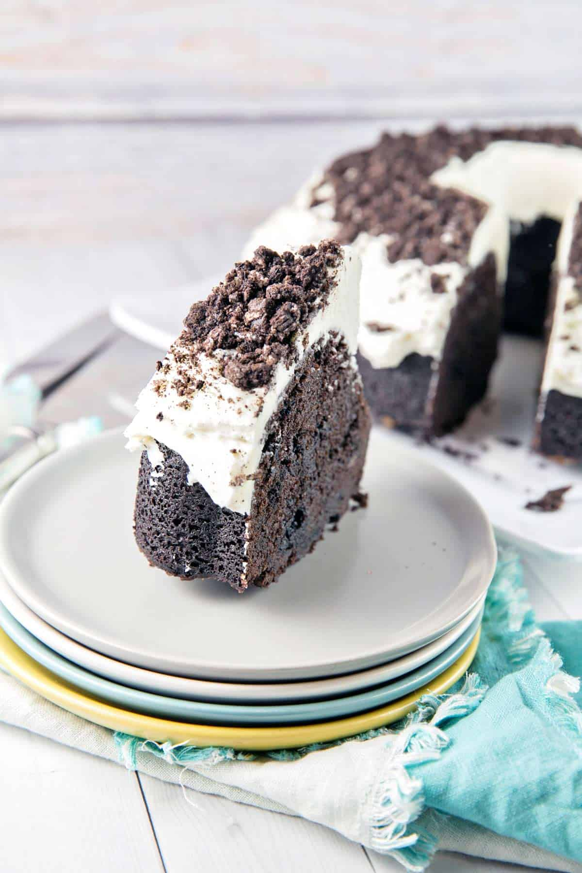 slice of cookies and cream oreo bundt cake on a stack of four dessert plates