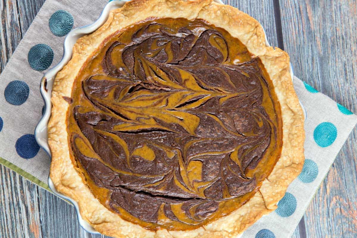 overhead image of a pumpkin pie baked with swirls of nutella