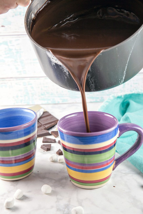 pouring extra thick hot chocolate from a saucepan into a mug