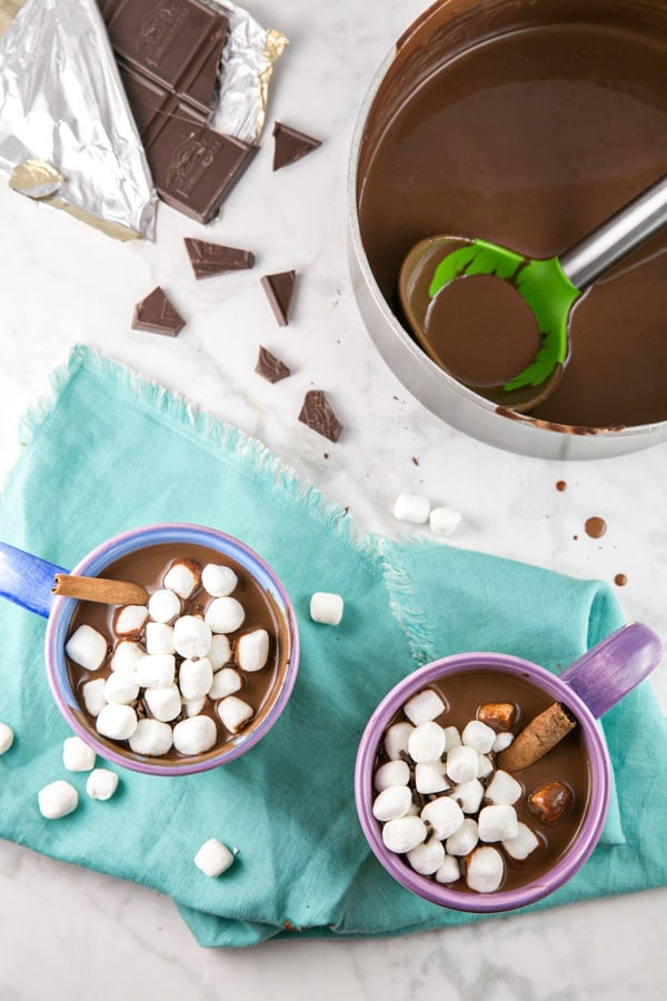 overhead view of a pot of hot chocolate and two mugs topped with miniature marshmallows