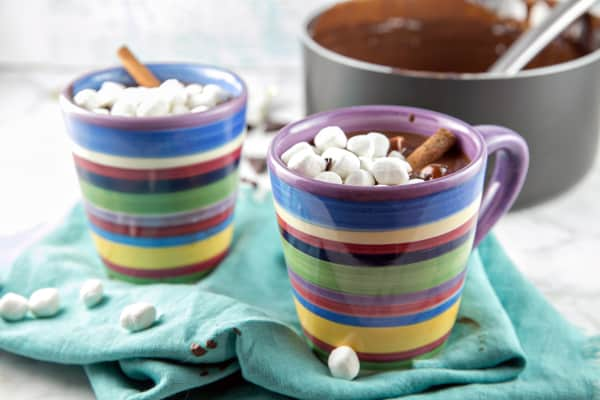 two mugs of thick hot chocolate topped with marshmallows and cinnamon sticks