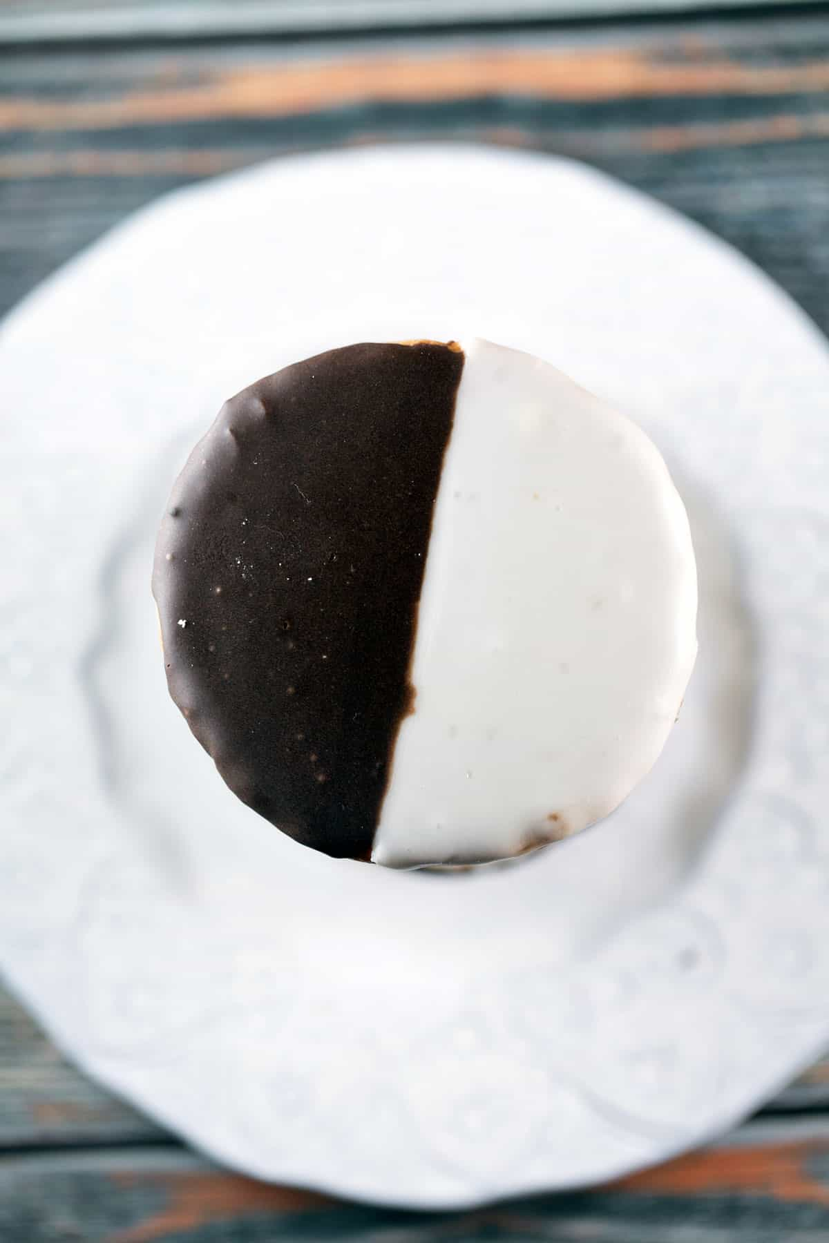 overhead view of a tall stack of black and white cookies on a white plate
