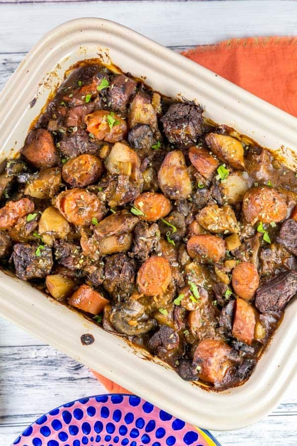 casserole dish filled with easy homemade instant pot beef stew on an orange placemat