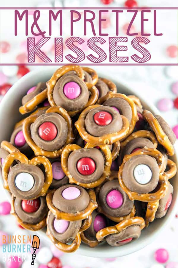 M&M Pretzel Kisses: a pretzel, a Hershey kiss, and a fun colored M&M -- so easy, but the bite-sized sweet and salty combination is irresistible.  Match M&M colors to holidays for a fun school treat! #bunsenburnerbakery #valentines #nobakedesserts #chocolate