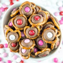M&M Pretzel Kisses: a pretzel, a Hershey kiss, and a fun colored M&M -- so easy, but the bite-sized sweet and salty combination is irresistible. Match M&M colors to holidays for a fun school treat! #dessert #valentines