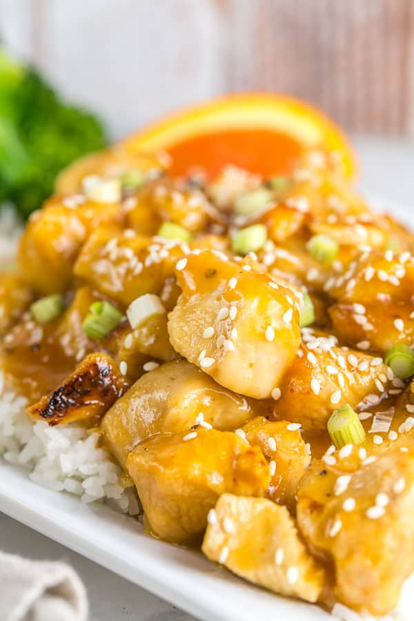 close up picture of orange chicken cooked in the instant pot covered with sauce and sesame seeds