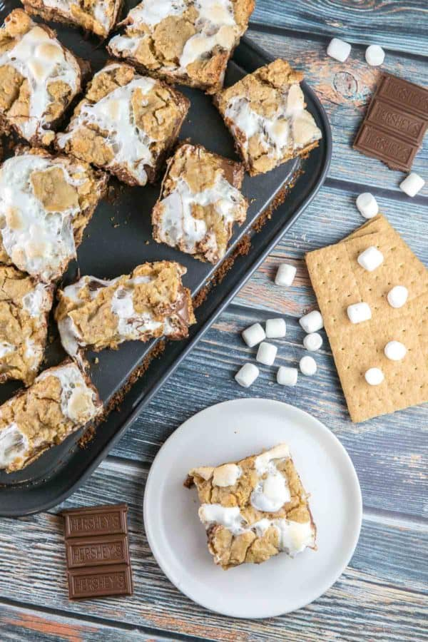 sliced bars on a baking sheet with marshmallows, graham crackers, and chocolate bars in the background