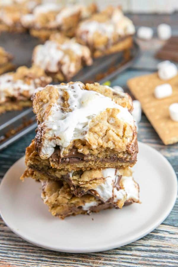 a stack of baked s'mores bars with gooey marshmallow on top