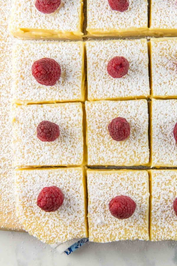 squares of lemon bars made with lemon pie filling and topped with raspberries