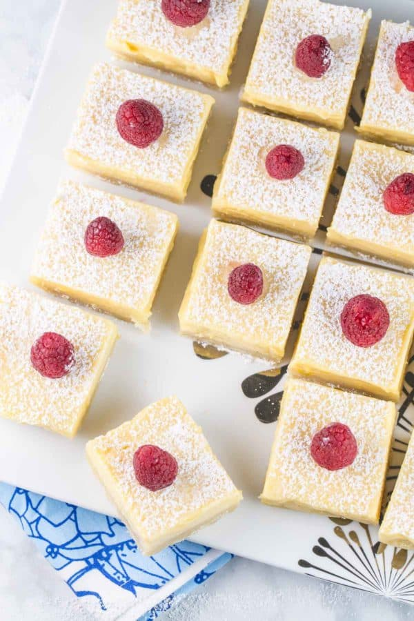 rows of lemon bars on a white serving plate