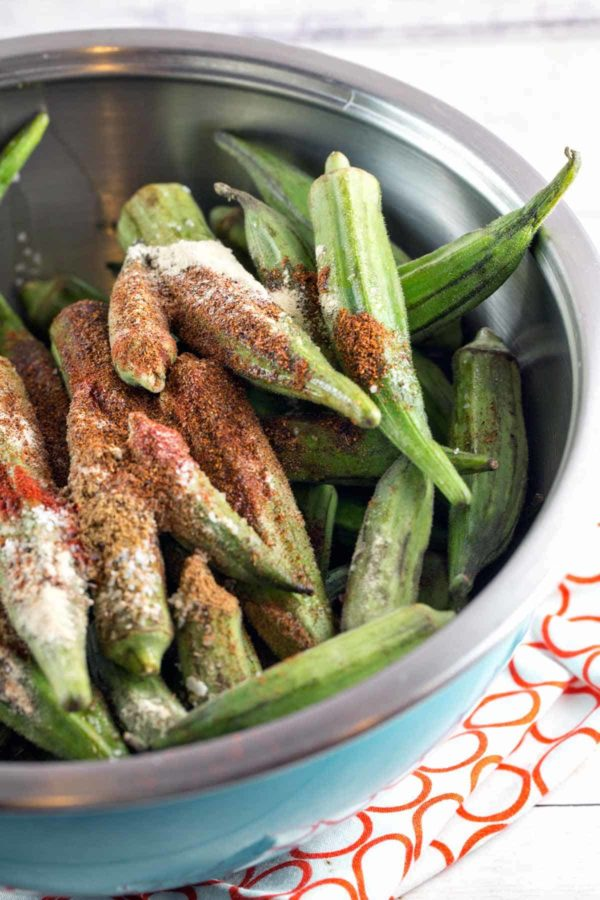 fresh bright green okra covered in spices and piled in a blue mixing bowl