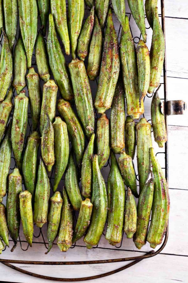 dozens of okra pods covered in spices lined up on a grill basket