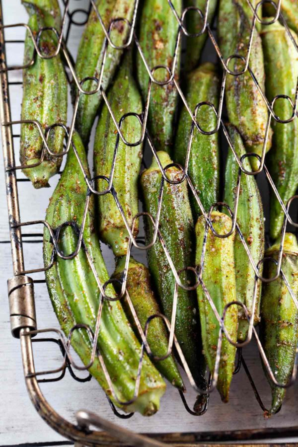 freshly grilled okra lined up in a single layer on a grilling basket