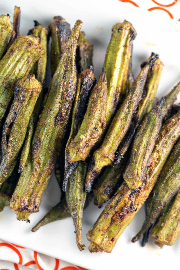 grilled okra covered in spices and stacked on a white serving dish