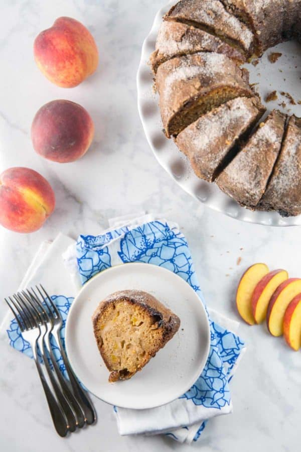 bundt cake cut into slices with one slice on a plate next to whole and sliced peaches