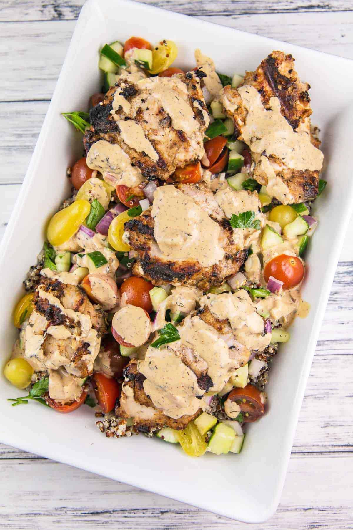 white serving dish filled with tomato cucumber salad, grilled chicken, and a creamy tahini sauce
