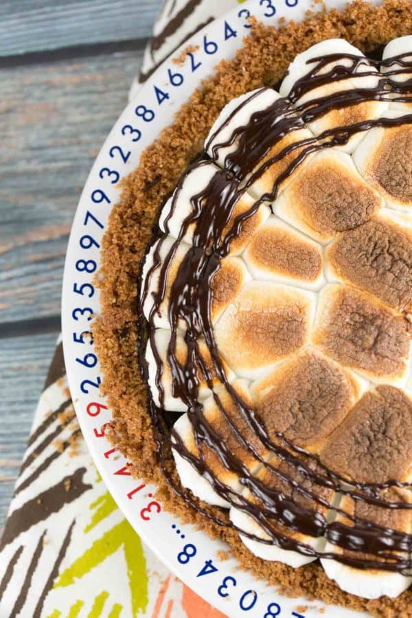 overhead view of s'mores pie with toasted marshmallows on top and a chocolate drizzle