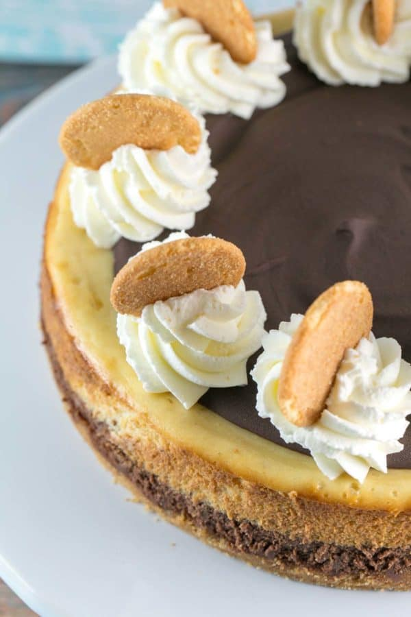 close up view of a chocolate banana cheesecake showing the swirls of whipped cream on top