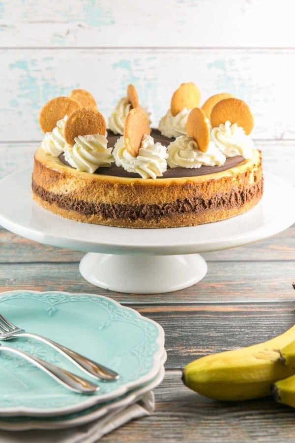 an uncut chocolate banana cheesecake highlighting the chocolate layer on the bottom and banana layer on the top