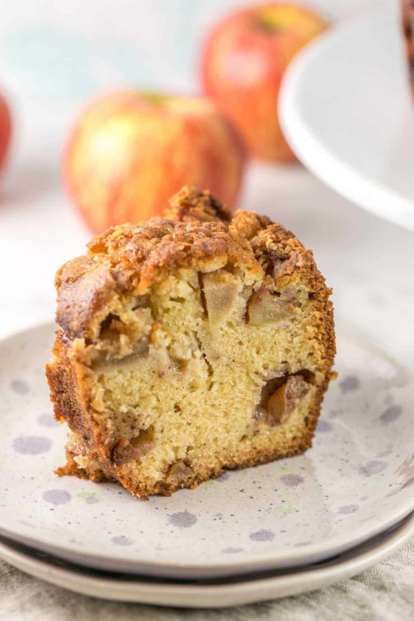 side view of a slice of jewish apple cake showing the big chunks of cinnamon covered apples and fine cake crumbs