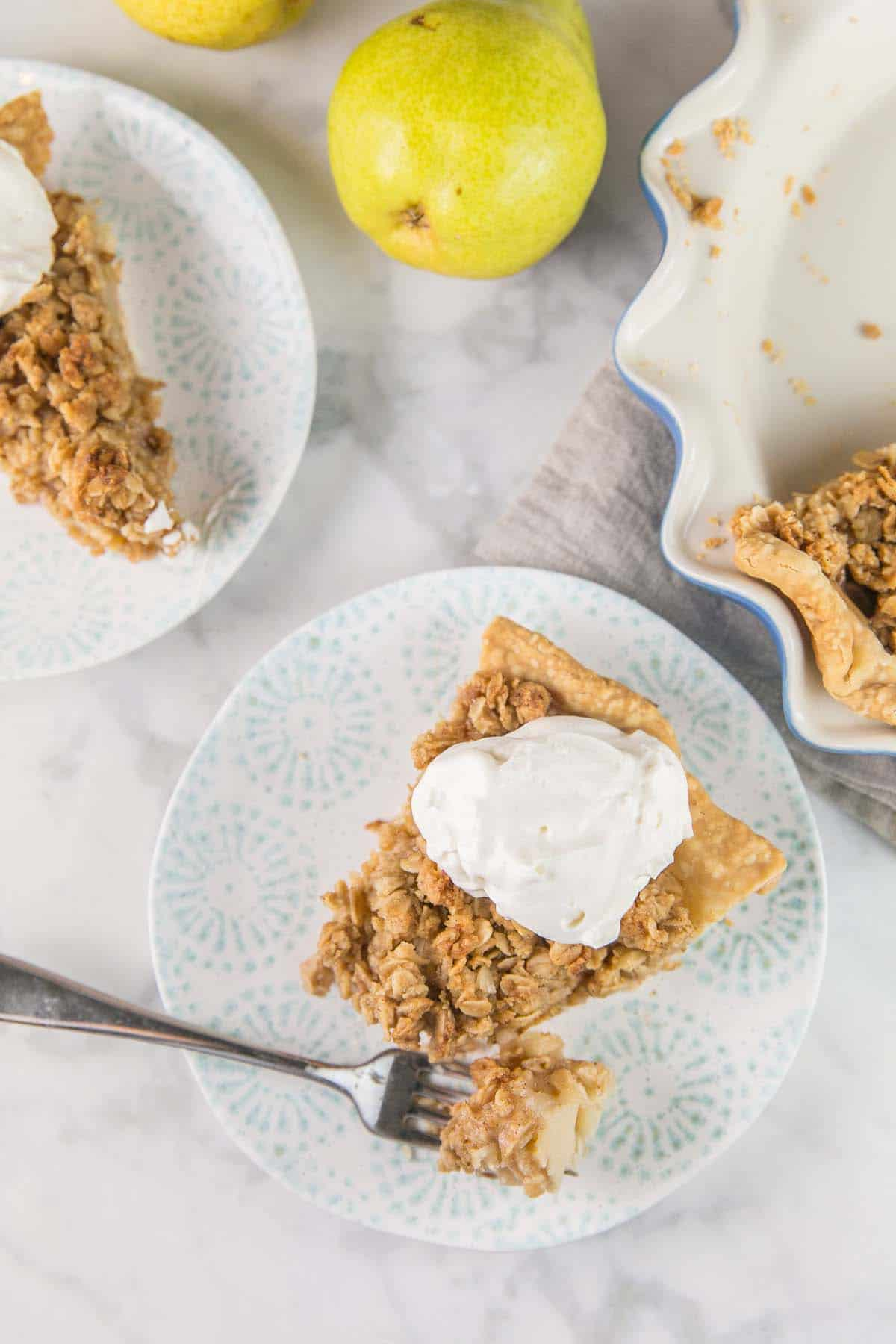 slices of caramel pear pie with a dollop of whipped cream on a blue and white plate with one forkful of pie removed