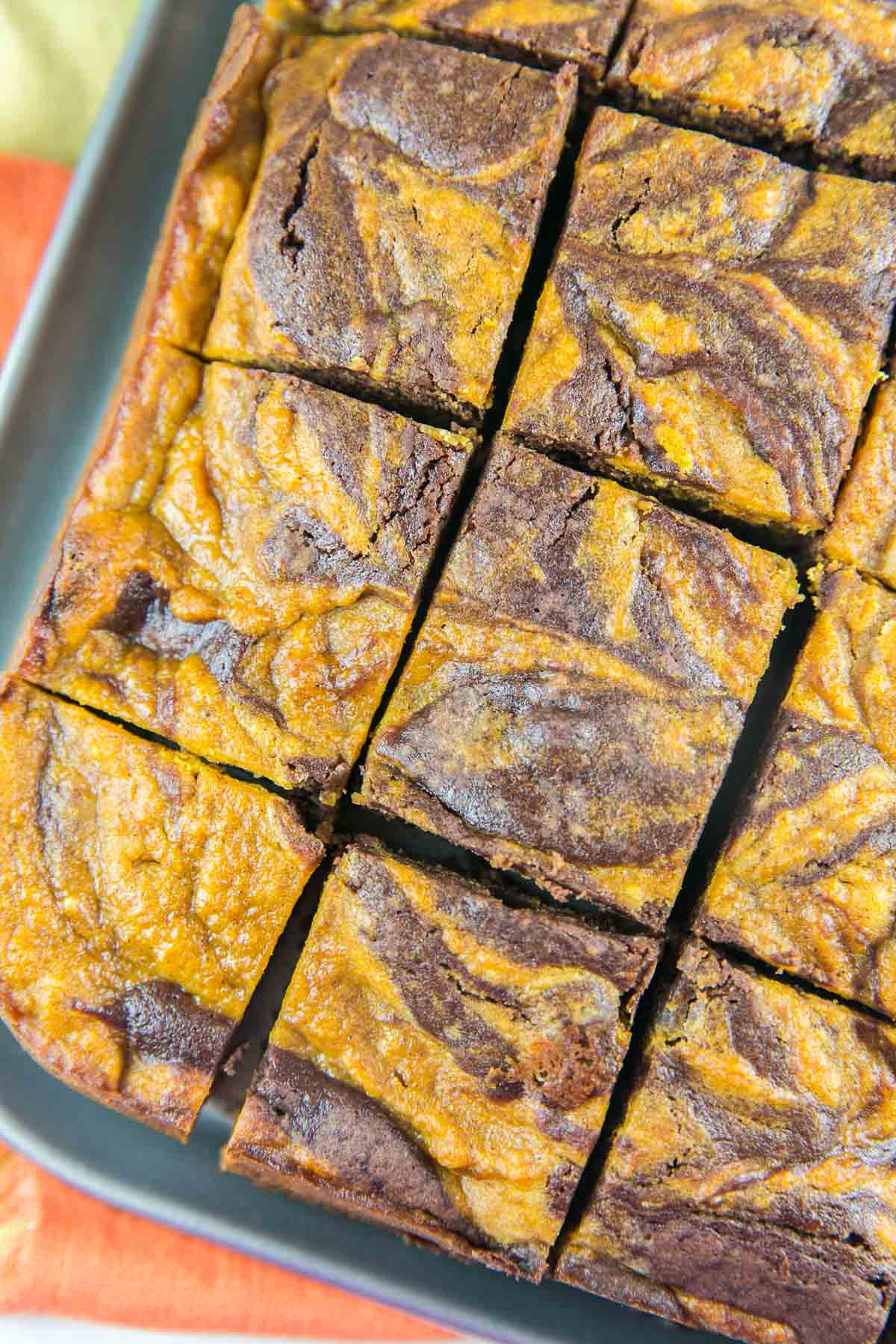 pumpkin swirl brownies cut into squares in a springform pan