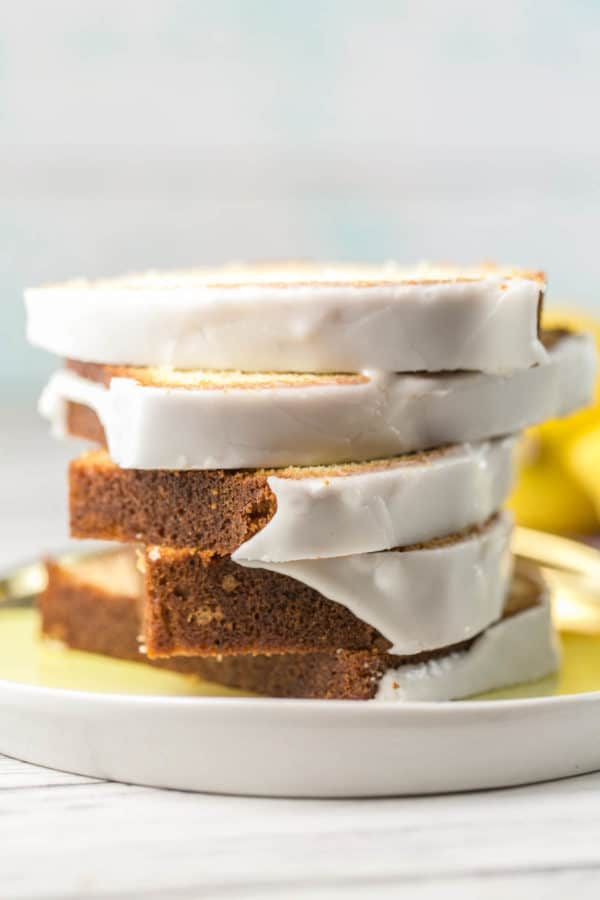 side view of five slices of glazed lemon pound cake stacked on a yellow plate