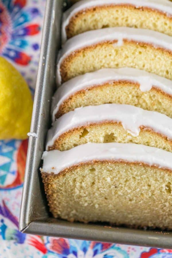 closeup view of slices of glazed lemon pound cake arrange in a loaf pan