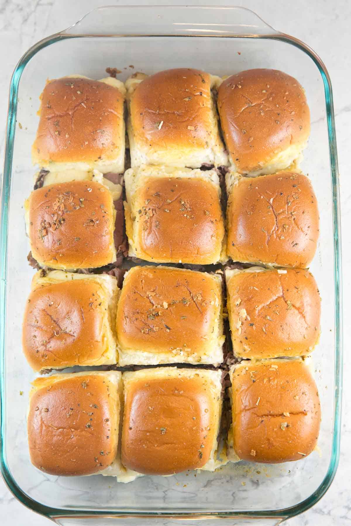overhead image of 12 baked roast beef sliders in a glass baking dish cut apart and ready to serve
