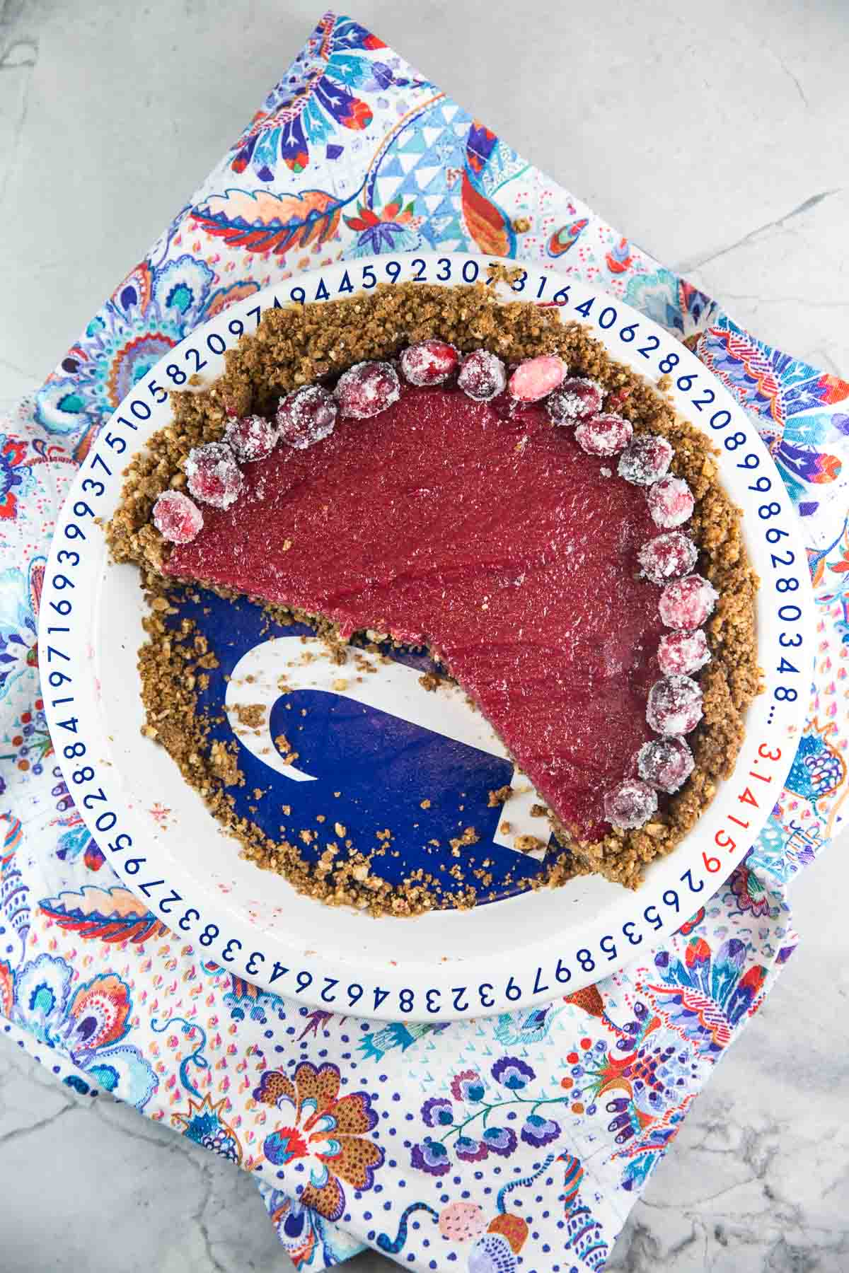 cranberry curd pie with a gingersnap crust in a pi-themed pi plate with a ring of sugared cranberries