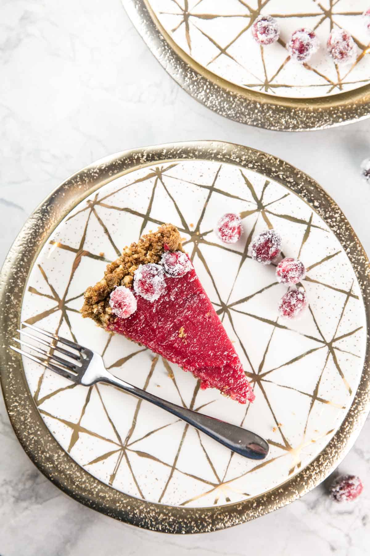 overhead view of one slice of cranberry curd pie on a gold and white plate surrounded by sugared cranberries