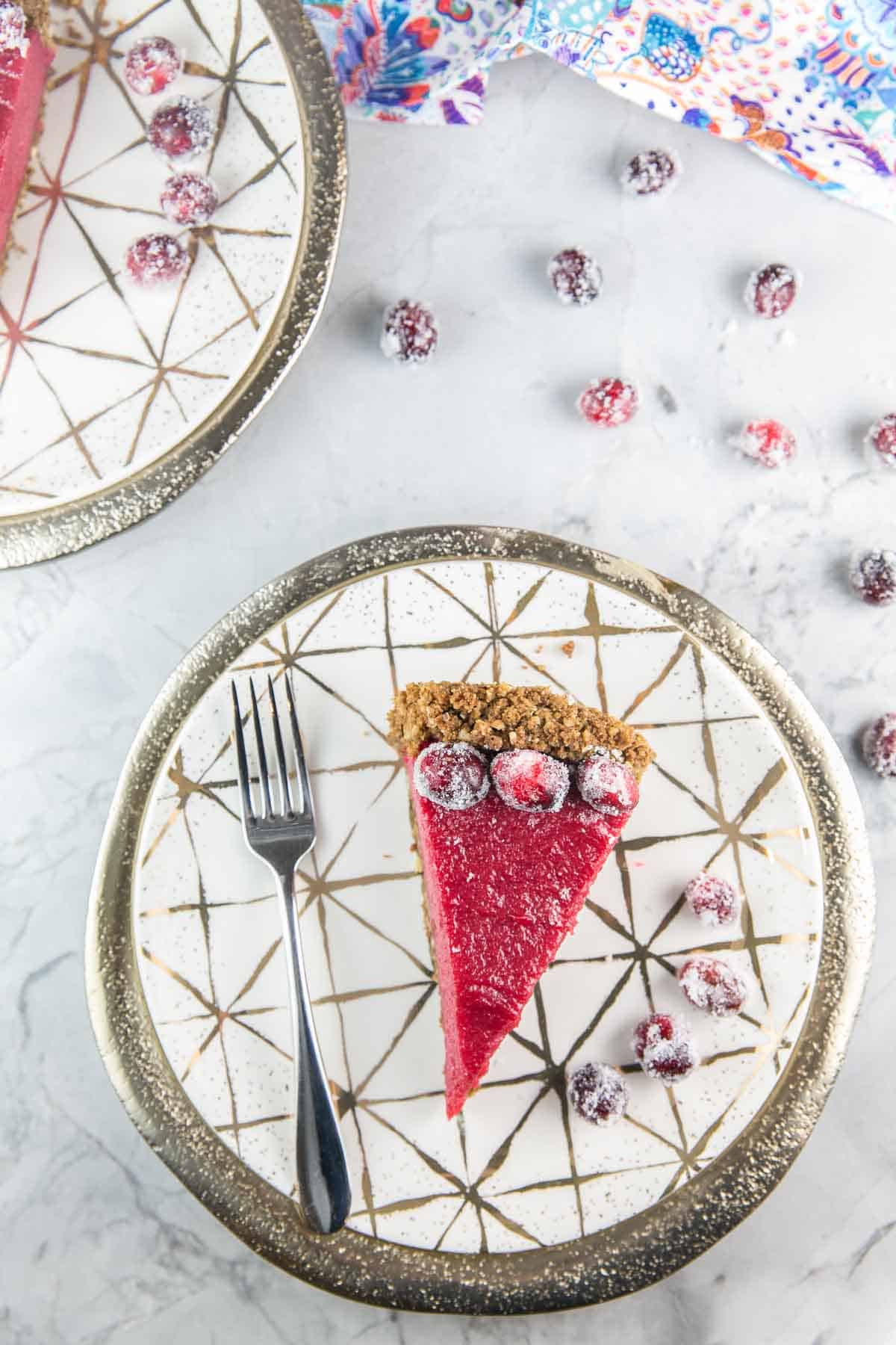 one slice of cranberry curd pie with a gingersnap hazel crust plated with sugared cranberries and a dessert fork