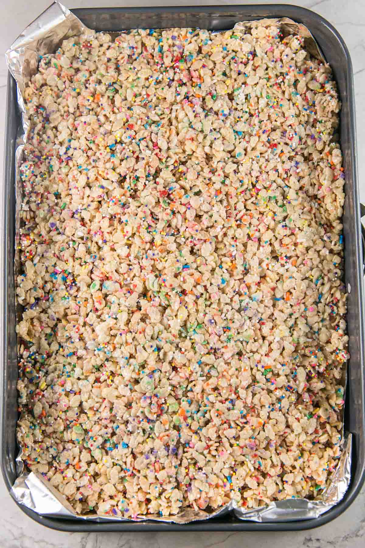 a large pan of uncut rice krispie treats mixed with rainbow sprinkles