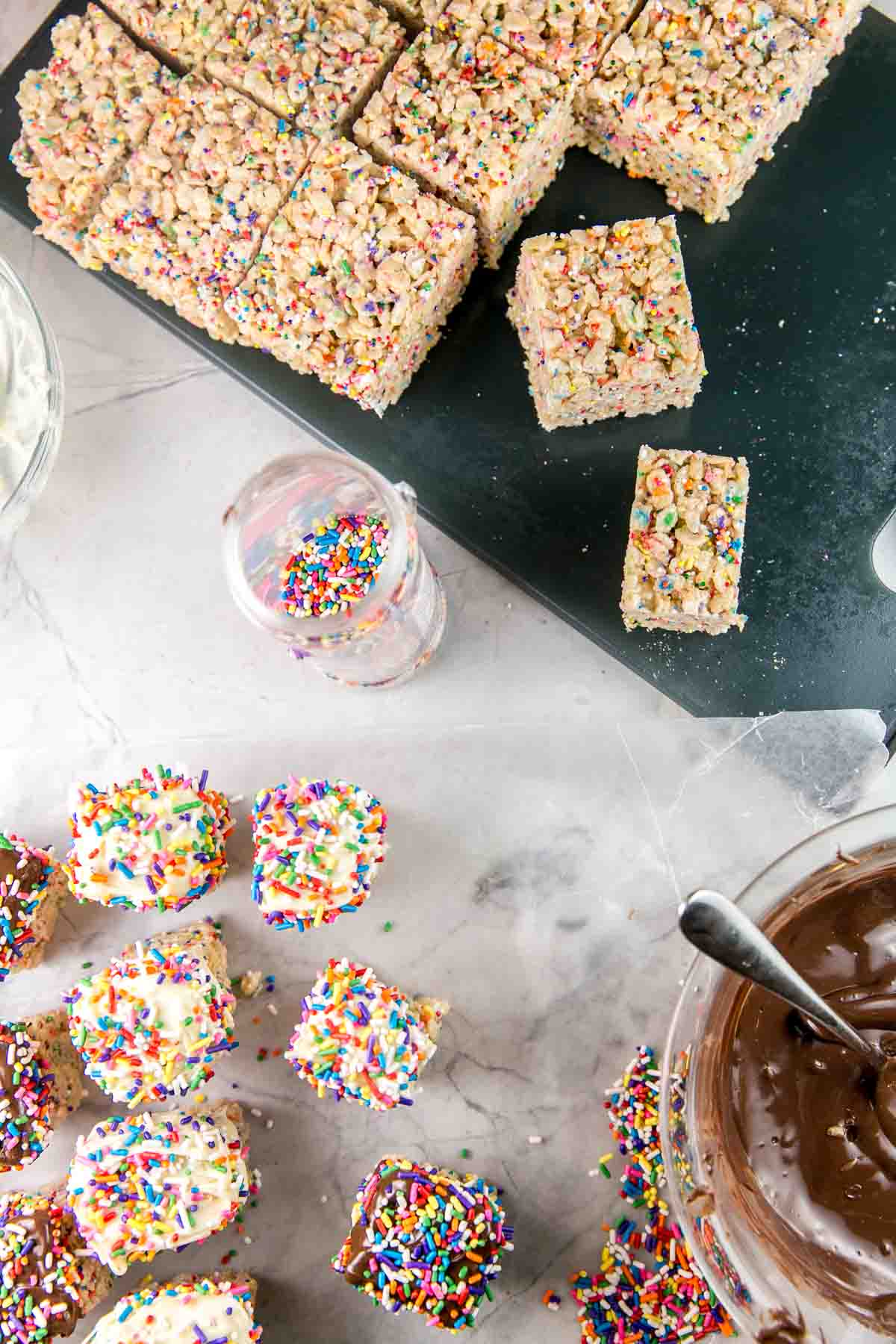 sprinkle rice krispie treats cut into small squares ready to dip in a bowl of melted chocolate
