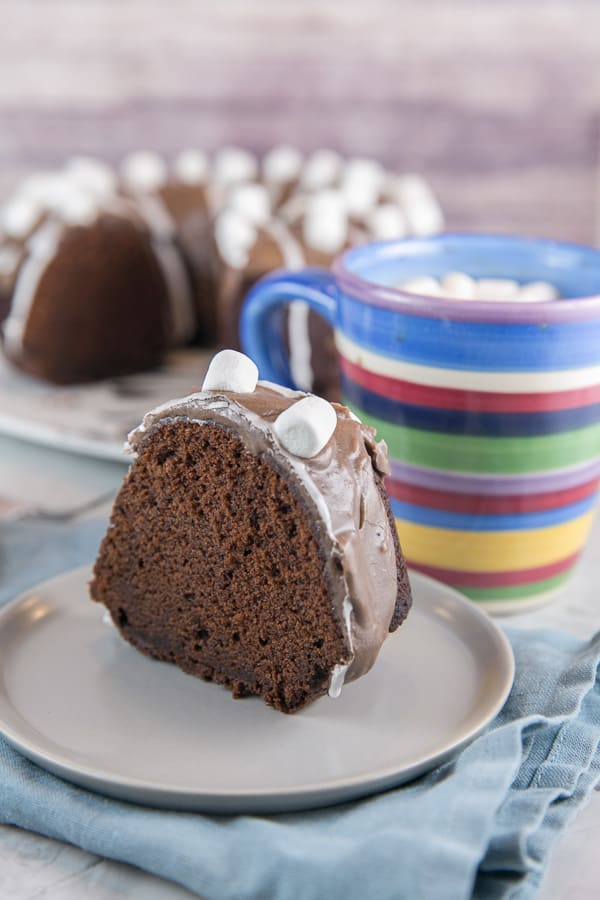 a slice of a hot chocolate bundt cake covered with miniature marshmallows next to a mug of hot chocolate