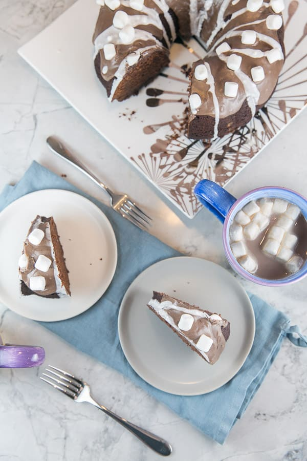 two slices of hot chocolate bundt cake covered with miniature marshmallows on white and grey dessert plates