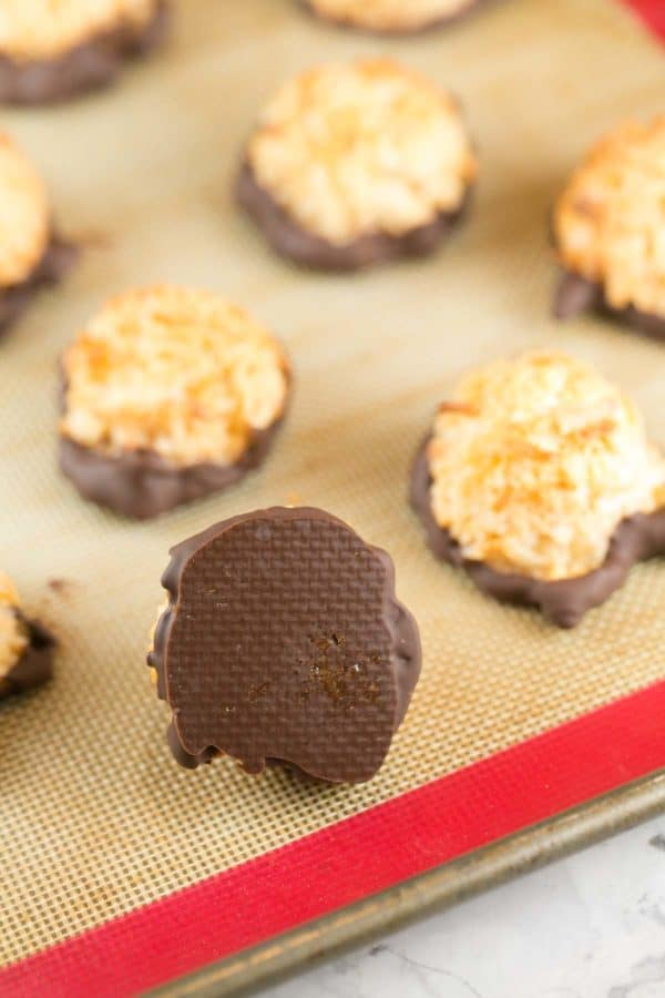 an upside-down chocolate dipped coconut macaroon showing how easily the melted chocolate comes off the baking sheet