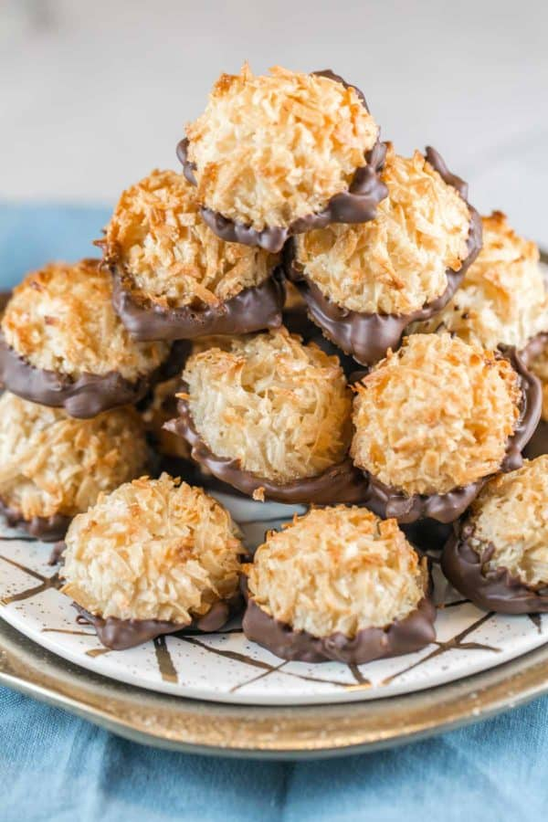 a tower of chocolate dipped coconut macaroons on a decorative white and gold plate
