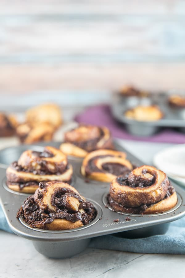 side view of babka muffins with chocolate swirls towering over the edge of a muffin tin