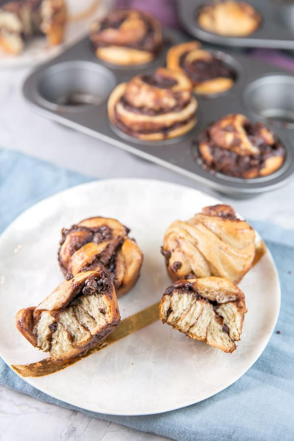 a chocolate babka muffin pulled open to show the layers of chocolate baked into the twisted dough