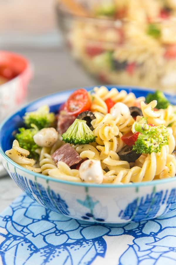 side view of a blue and white bowl filled with a heaping pile of colorful italian pasta salad
