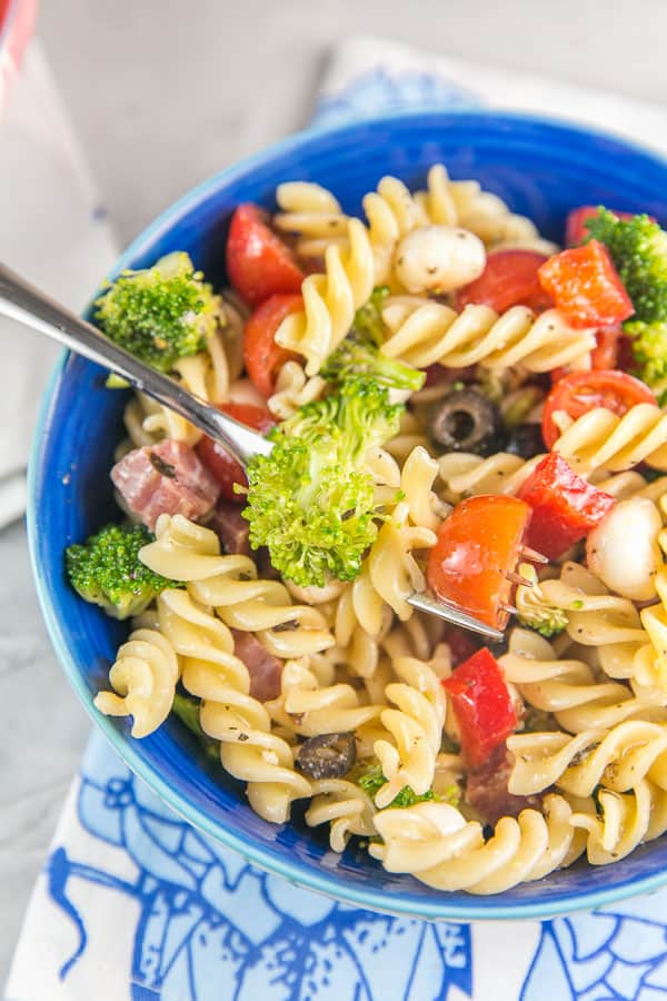 overhead view of a bowl of italian pasta salad with rotini, broccoli, red peppers, olives, and salami visible
